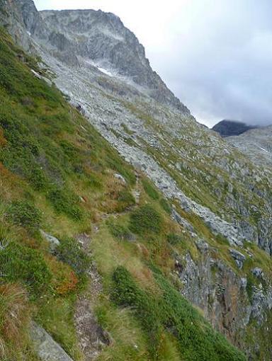 Au-dessus du ressaut rocheux, progression sur un sentier horizontal au-dessus d`à-pics, face au Grand Quayrat