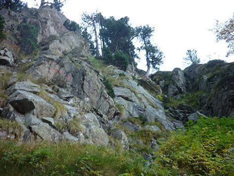 En haut du raide vallon, une flêche rouge peinte sur un rocher invite à virer à droite
