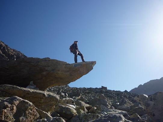 Dans la vaste zone d`éboulis de gros blocs de granit, passage sur un énorme bloc en équilibre