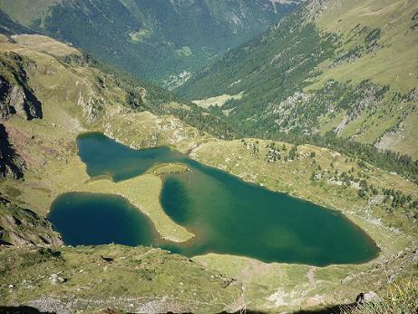 En contrebas du sentier taillé dans la falaise, le lac Vert