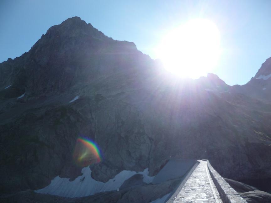 Traversée du barrage du lac du Portillon, face au pic Lézat et au soleil